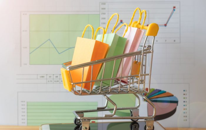 Retail shopping cart with gift bags placed on top of an iPhone. Background is data charts and graphs